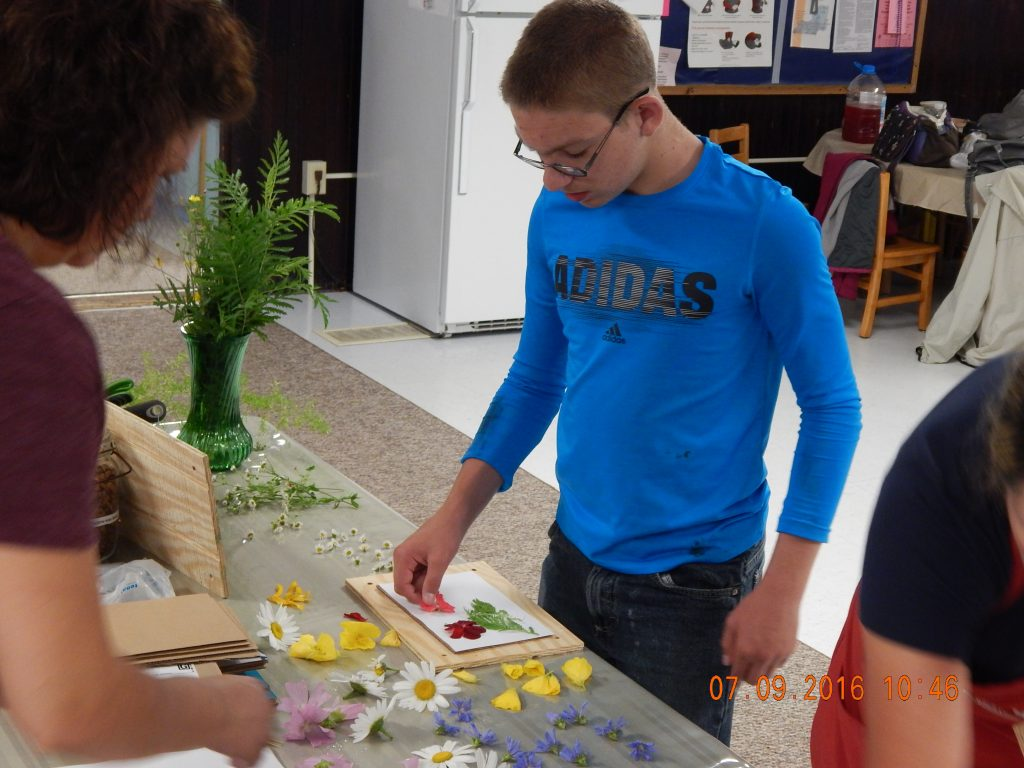 Jacob is creating more beauty using flowers from the garden pressed on paper. He is encouraged by Master Gardeners, involved in the Community Garden project at Dannemora Methodist Church.